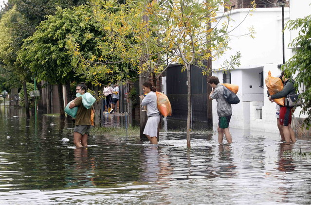 Residents carry their belongings through a street after heavy rains flooded a large part of the city, in La Plata April 3, 2013. At least 35 people were killed in Argentina on Wednesday after a torrential downpour battered the eastern city of La Plata and forced some 2,200 people to flee their homes in search of dry ground. (Photo by Enrique Marcarian/Reuters)