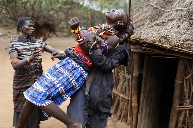 A man holds a girl as she tries to escape when she realised she is to to be married, about 80 km (50 miles) from the town of Marigat in Baringo County, Kenya,  December 7, 2014. As Pokot tradition dictates, the future husband arrived to her family home with a group of men to collect the girl. The men arrived with the last settled dowry of livestock for the girl's family.  (Photo by Siegfried Modola/Reuters)