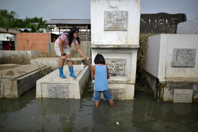 Residents offer candles at the grave of a departed loved one inside a flooded cemetery in Calumpit town, Bulacan province, north of Manila November 1, 2015. (Photo by Ezra Acayan/Reuters)
