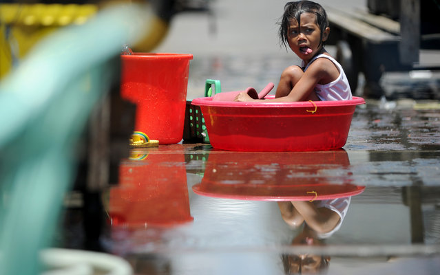 A girl cools off in a water basin in Manila on April 19, 2013. The Philippines has been experiencing the hottest days of the year with temperatures of 35 degrees Celsius (95 Fahrenheit) recorded in parts of the city. (Photo by Noel Celis/AFP Photo)