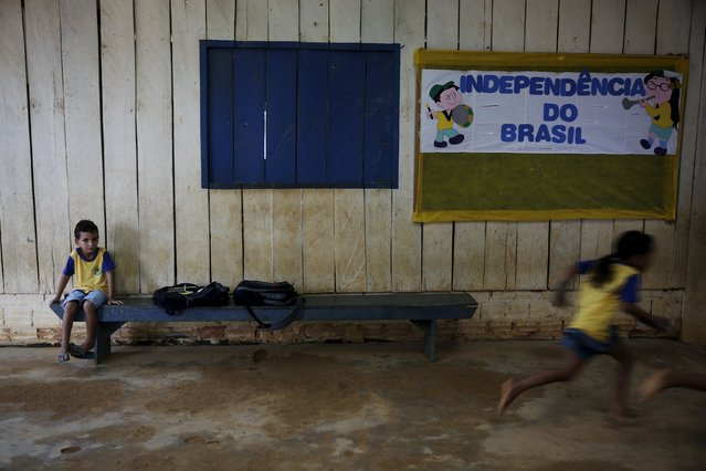 A boy sits as other children run in the corridors of their school in the village of Rio Pardo next to Bom Futuro National Forest, in the district of Porto Velho, Rondonia State, Brazil, August 31, 2015. (Photo by Nacho Doce/Reuters)