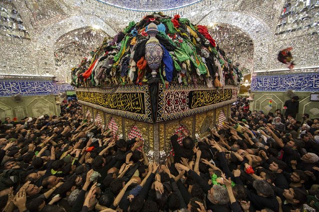 Shi'ite Muslim pilgrims reach out to touch the tomb of Imam al-Abbas located inside the Imam al-Abbas shrine to mark Arbain in the holy city of Kerbala, southwest of Baghdad December 13, 2014. Iraqi officials say millions of Shi'ite pilgrims from across Iraq and neighbouring countries are expected in Kerbala for Saturday's Arbain ritual, which marks the last of 40 days mourning for the death 1,300 years ago of Imam Hussein. (Photo by Reuters/Stringer)