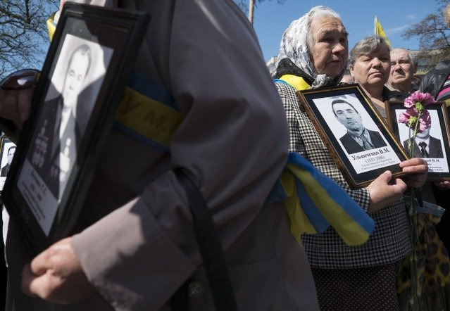 Women hold portraits of their relatives, victims of the Chernobyl nuclear disaster, during a ceremony in Kiev April 26, 2013. Belarus, Ukraine and Russia marked the 27th anniversary of the Chernobyl disaster, the world's worst civil nuclear accident, on Friday. (Photo by Gleb Garanich/Reuters)