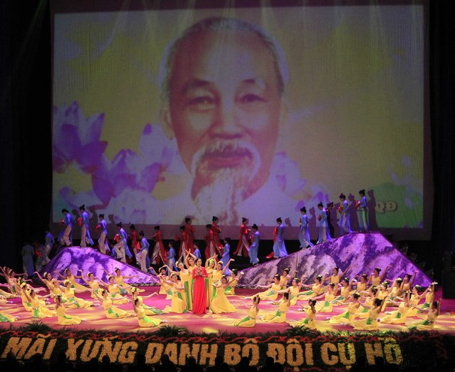 People perform in front of a screen showing an image of late revolutionary leader Ho Chi Minh during celebrations to commemorate the 70th anniversary of the establishment of the Vietnam People's Army at the National Convention Center in Hanoi December 20, 2014. (Photo by Reuters/Kham)
