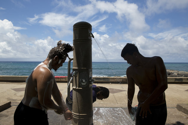 In this Tuesday, August 25, 2015 photo, from left, John Tuilata, Tiare Talo and Roy Kalama, wash themselves using public showers in Kakaako Waterfront Park in Honolulu. The three live in a homeless encampment in Honolulu's Kakaako district. Homelessness in Hawaii has grown in recent years, leaving the state with 487 homeless per 100,000 people, the nation's highest rate per capita, ahead of New York and Nevada, according to federal statistics. (Photo by Jae C. Hong/AP Photo)