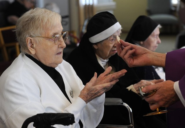 Sister Mary Paula Thompson receives the Eucharist during services at Our Lady of Rickenbach health care facility that is part of the Benedictine Sisters of Perpetual Adoration monastery in Clyde, Missouri, December 18, 2014. (Photo by Dave Kaup/Reuters)
