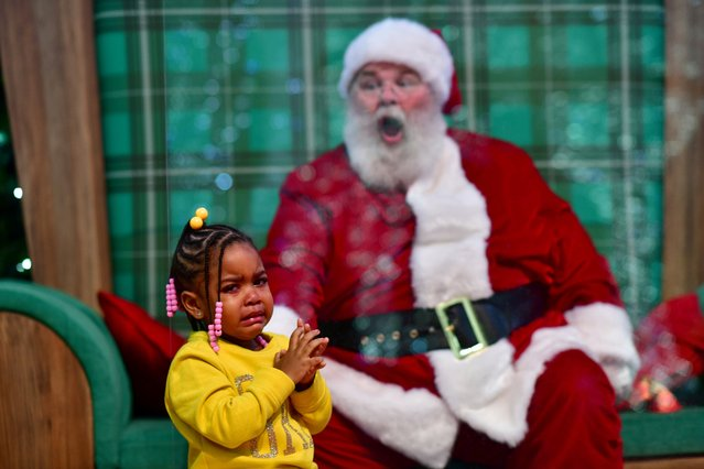 Majesty Davis, 3, cries while visiting Santa Claus, who sits behind a plexiglass divider due to the coronavirus disease (COVID-19) pandemic, at the Willow Grove Park Mall in Willow Grove, Pennsylvania, U.S. November 14, 2020. (Photo by Mark Makela/Reuters)