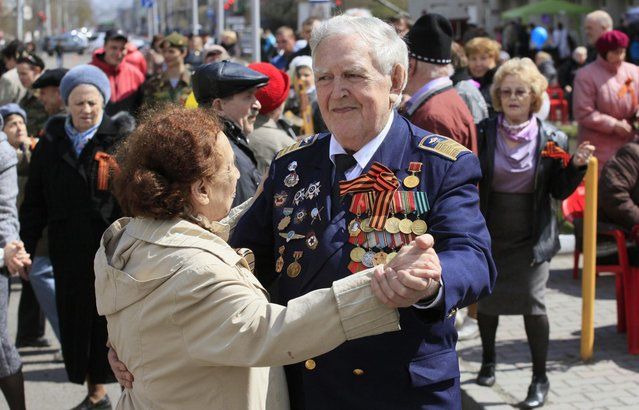 World War Two veteran Michael Tarskikh and his wife Irina, both 87, take part in a street dancing event on the eve of Victory Day in Russia's Siberian city of Krasnoyarsk, May 8, 2013. Tarskikh made 227 night flights on a Po-2 biplane across the front line for surveillance and photographing of Nazis target during World War Two in Belarus, Lithuania and East Prussia, took part in a storm of Konigsberg (Kaliningrad) and finished the war in the Baltic port of Danzig (Gdansk). Russia marks victory over Nazi Germany on May 9. (Photo by Ilya Naymushin/Reuters)