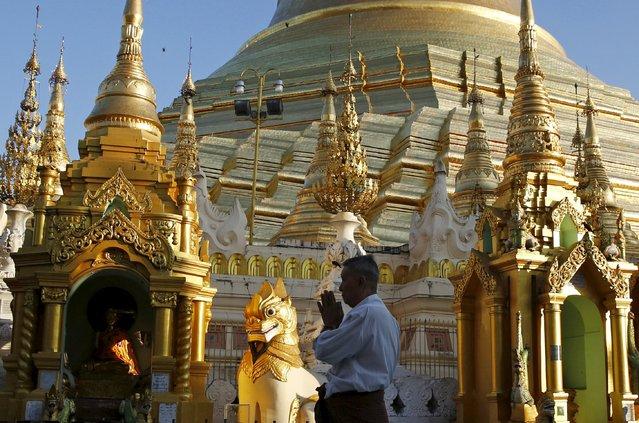 A man prays as he walks around Shwedagon Pagoda in Yangon, Myanmar, November 13, 2015. (Photo by Olivia Harris/Reuters)