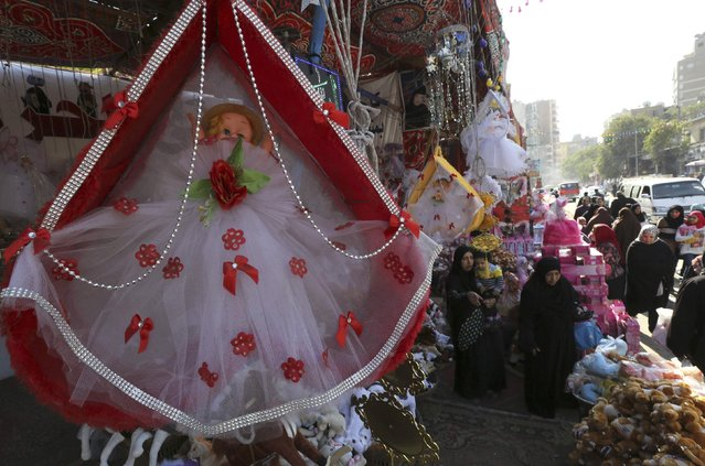"Women buy traditional sweets and doll toys for children to celebrate the birthday of prophet Muhammad, also known as ""mawlid al nabi"", which will fall next week, in a makeshift tent in Cairo, December 30, 2014. (Photo by Mohamed Abd El Ghany/Reuters)"