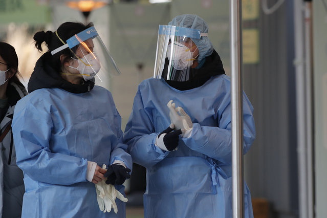 Medical workers wearing protective gears in the sub-zero temperatures talk at coronavirus testing site in Seoul, South Korea, Monday, December 21, 2020. (Photo by Lee Jin-man/AP Photo)