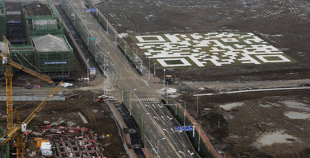 A giant QR code is seen near a housing construction site, owned by Chinese developer Vanke in Hefei in central China's Anhui province, on May 17, 2013. The 6,400-square-meter QR code, made with marbles and lawn, can be scanned from the air by mobile phone and takes visitors to a website that's intended to attract home buyers to the housing project, according to local media. (Photo by Associated Press)
