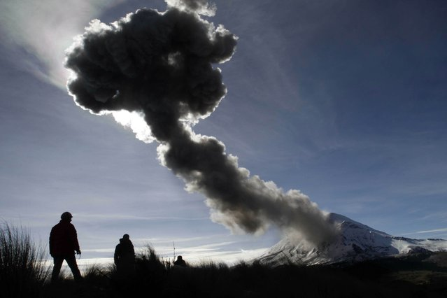 People look at the Popocatepetl volcano as it spews ash from the Paso de Cortes community, in Puebla State, Mexico on December 28, 2014. (Photo by Guadalupe Perez/AFP Photo)