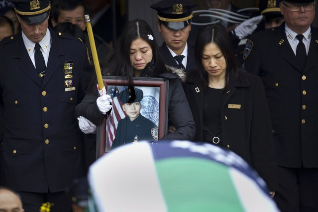 Widow Pei Xia Chen holds a photo of slain New York Police Department officer Wenjian Liu as his casket departs his funeral in the Brooklyn borough of New York January 4, 2015. New York Mayor Bill de Blasio appealed for reconciliation on Sunday in his eulogy for the second of two police officers murdered last month, two deaths that led to accusations the mayor had contributed to an anti-police climate. (Photo by Carlo Allegri/Reuters)