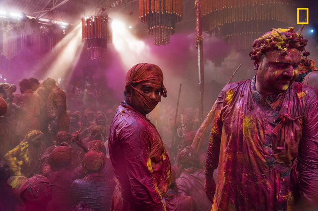 """""""Lath mar Holi is a local celebration of the Hindu festival of Holi. It takes place days before the actual Holi in the neighboring towns of Barsana and Nandgaon near Mathura in the state of Uttar Pradesh, where thousands of Hindus and tourists congregate, each year"""". (Photo by Sampa Guha Majumdar/National Geographic Travel Photographer of the Year Contest)"""