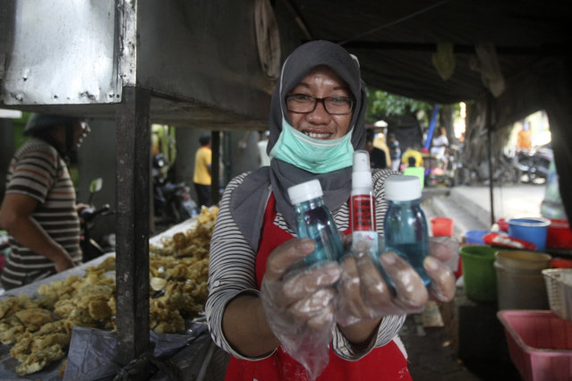 In this Thursday, March 26, 2020 photo, a street food vendor shows hand sanitizers and soaps distributed by student activists in Yogyakarta, Indonesia. A group of students from several universities in the central Java city has distributed soaps and hand sanitizers to informal daily workers whose incomes are affected by the coronavirus outbreak. (AP Photo/Fahmi Rosyidi)