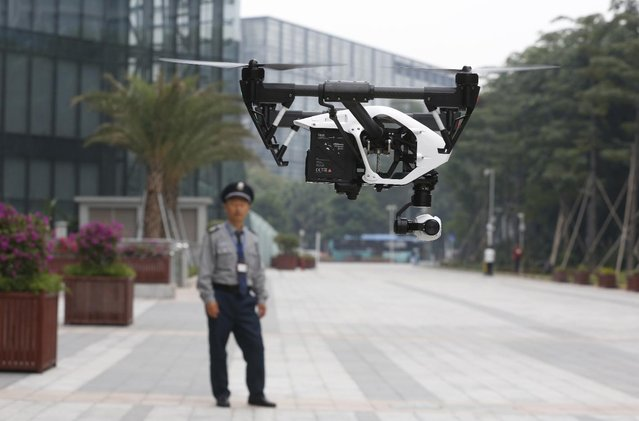 In this Monday, December 15, 2014 photo, a security guard watches a demonstration of a DJI Technology Co. Inspire 1 drone in Shenzhen, south China's Guangdong province. (Photo by Kin Cheung/AP Photo)