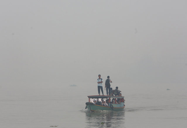 In this Thursday, September 17, 2015 file photo, students ride on a boat on their way to school while haze from wildfires blanket the Musi River in Palembang, South Sumatra, Indonesia. (Photo by Tatan Syuflana/AP Photo)