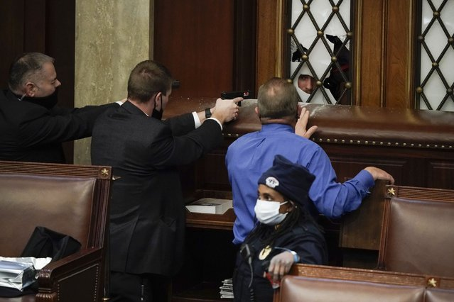Police with guns drawn watch as protesters try to break into the House Chamber at the U.S. Capitol on Wednesday, January 6, 2021, in Washington. (Photo by J. Scott Applewhite/AP Photo)