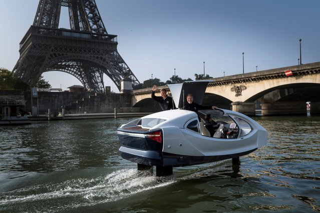 """Sea Bubbles start-up founders Alain Thebault (L) and Anders Bringdal (R) stand on board a Sea Bubble electric maritime """"flying taxi"""" during a demonstration on May 20, 2018 on the river Seine in Paris, in front of the Eiffel Tower. Aeronautical engineers and watermen Anders Bringdal and Alain Thebault are co-founders and developers of the Sea Bubbles zero-impact transportation ecosystem. (Photo by Lionel Bonaventure/AFP Photo)"""