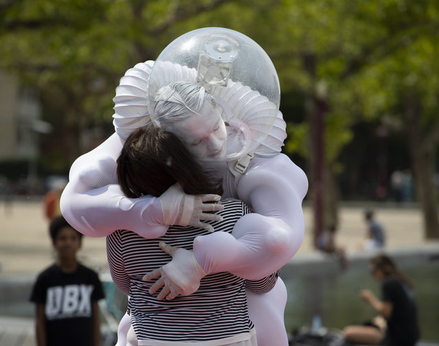 """A tourist gets an """"Art Hug"""" from a disinfected costumed man outside the reopened Rijksmuseum in Amsterdam, Netherlands, Monday, June 1, 2020. The government takes a major step to relax the coronavirus lockdown, with bars, restaurants, cinemas and museums reopening under strict conditions. (Photo by Peter Dejong/AP Photo)"""