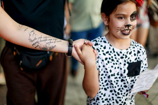 """A girl attends a rally held the day before the start of the Paris Climate Change Conference (COP21), in Santiago, Chile November 29, 2015. In the tatoo reads, """"To much little people, at the little places, doing little things, can change the world. Galeano"""". (Photo by Pablo Sanhueza/Reuters)"""