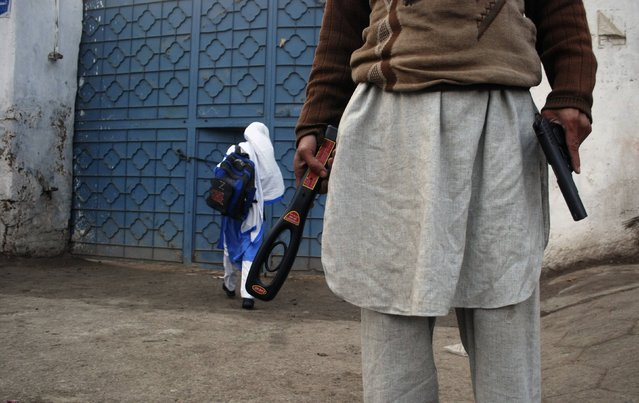 A man with a gun and a metal detector poses for photographers (unseen) while he stands outside a school after it reopened in Peshawar January 12, 2015. Children streamed back to school across Pakistan on Monday in an anxious start to a new term following last month's massacre of 134 students at an army-run school in the volatile northwestern city of Peshawar. (Photo by Khuram Parvez/Reuters)