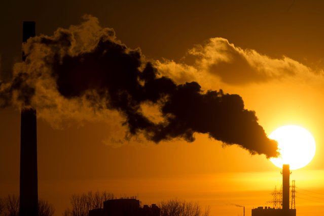 The sun sets behind powerplant smokestacks in Toronto, Friday, January 16, 2015. (Photo by Frank Gunn/AP Photo/The Canadian Press)