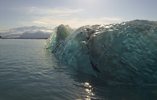 """Flipped Iceberg"". I was riding a zodiac through Jökulsárlón Glacier Lagoon and found this recently flipped iceberg – I loved seeing the frozen bubbles and the glassy appearance. Location: Jökulsárlón Glacier Lagoon, Iceland. (Photo and caption by Christine Baum/National Geographic Traveler Photo Contest)"