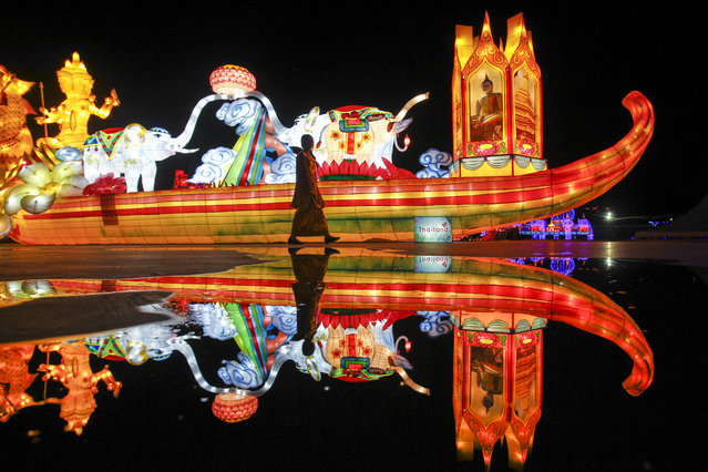 A woman walks past an illuminated decoration symbolising Thailand during a light show in Kuala Lumpur, Malaysia, Tuesday, December 8, 2015. The light show features the different countries of ASEAN. (Photo by Joshua Paul/AP Photo)