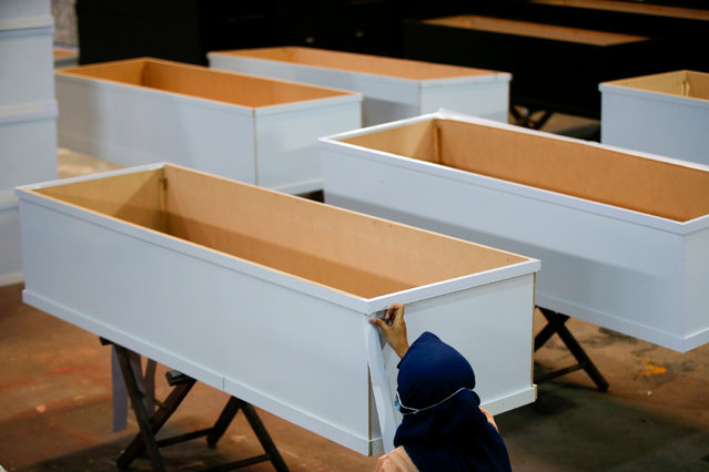 A worker assembles a coffin for the victim of coronavirus disease (COVID-19) at a furniture workshop, as the outbreak continues, in Tangerang, on the outskirts of Jakarta, Indonesia, February 3, 2021. (Photo by Willy Kurniawan/Reuters)