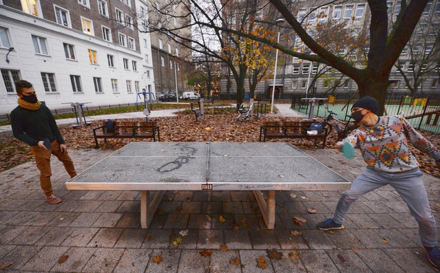 Two men play table tennis in a city square in Warsaw, Poland, Saturday, November 7, 2020. Due to the increase in coronavirus cases, the government introduced new restrictions in shops, schools and cultural institutions through November. (Photo by Czarek Sokolowski/AP Photo)