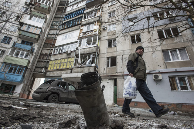 A man walks by a burned car and a piece of exploded Grad missile, outside an apartment building in Vostochniy district of Mariupol, Eastern Ukraine, Sunday, January 25, 2015. (Photo by Evgeniy Maloletka/AP Photo)