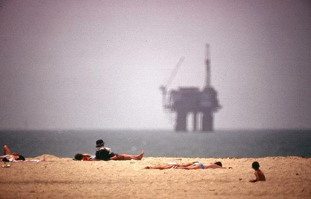 Sunbathers at Huntington Beach, California, an oil platform visible in the distance, May 1975. (Photo by Charles O'Rear/NARA via The Atlantic)
