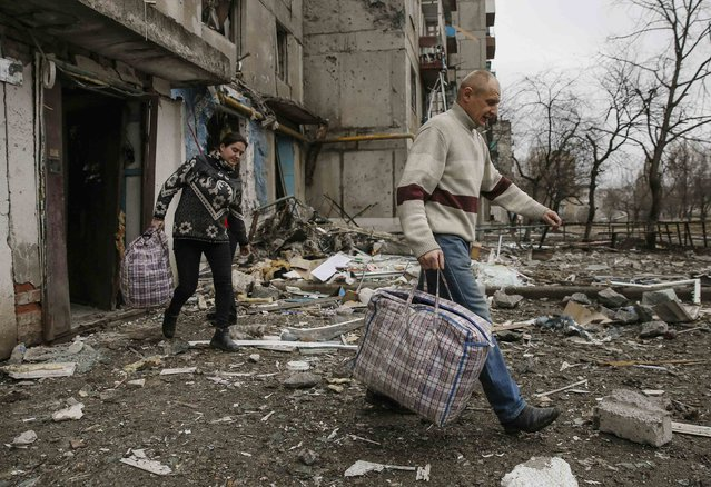 Local residents leave a residential block during a recent shelling, in the town of Yenakieve, northeast from Donetsk, February 2, 2015. (Photo by Maxim Shemetov/Reuters)