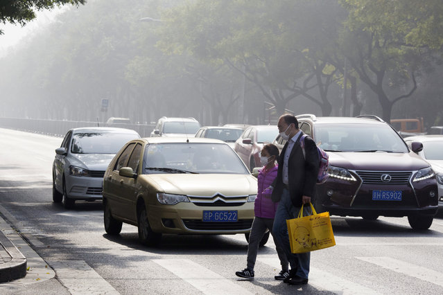 A man and a child wear masks during a heavily polluted day in Beijing, China, Saturday, November 5, 2016. China's cabinet has issued a new climate plan targeting an 18-percent cut in carbon emissions by 2020 compared to 2015 levels. (Photo by Ng Han Guan/AP Photo)