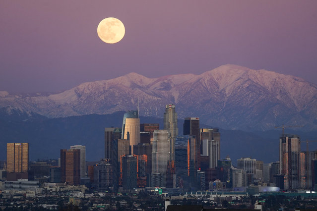 The moon rises over snow covered mountains, behind the downtown Los Angeles skyline Tuesday, December 29, 2020, in Los Angeles. (Photo by Ashley Landis/AP Photo)