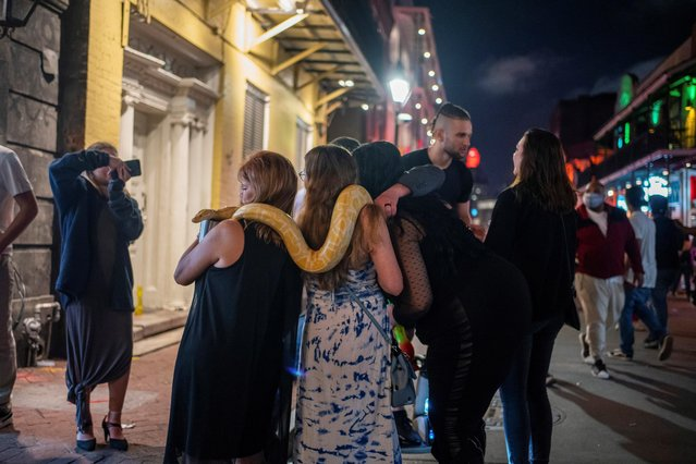 People handle an albino Burmese python on Bourbon Street as the coronavirus disease (COVID-19) restrictions are eased in New Orleans, Louisiana, U.S., March 13, 2021. (Photo by Kathleen Flynn/Reuters)