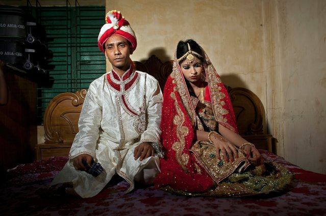 Mohammad Hasamur Rahman, 32, poses for photographs with his new bride, 15-year-old Nasoin Akhter, August 20, 2015, in Manikganj, Bangladesh. (Photo by Allison Joyce/Getty Images)