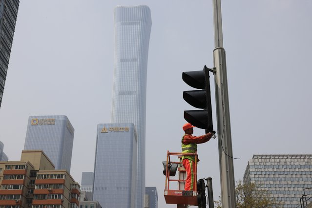 A worker installs new traffic lights at a junction in Beijing on Thursday, April 15, 2021. (Photo by Ng Han Guan/AP Photo)