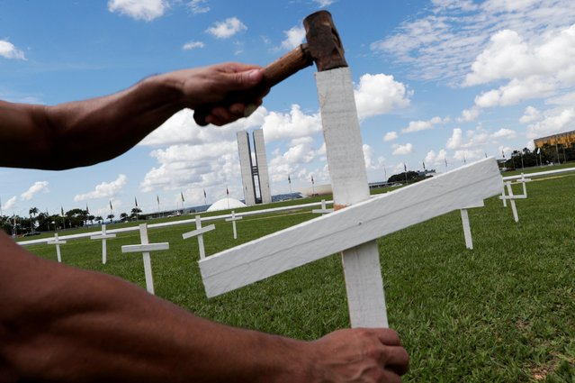 A demonstrator places a cross symbolising the ones who died from the coronavirus disease (COVID-19) in front of the National Congress in Brasilia, Brazil on April 27, 2021. (Photo by Ueslei Marcelino/Reuters)