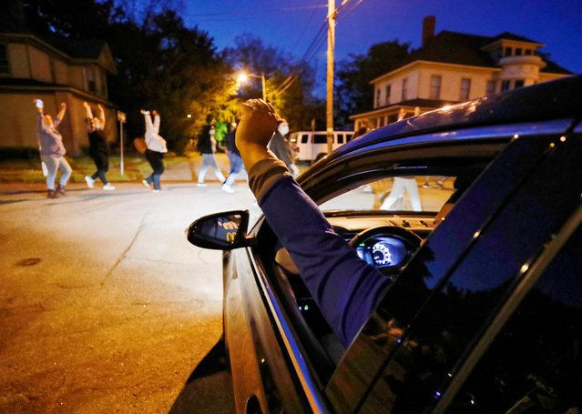 A motorist raises her fist in support of passing protesters marching in the evening after family members were shown body camera footage of a deputy sheriff shooting and killing 42-year-old Black man Andrew Brown Jr. last week, in Elizabeth City, North Carolina, April 26, 2021. (Photo by Jonathan Drake/Reuters)