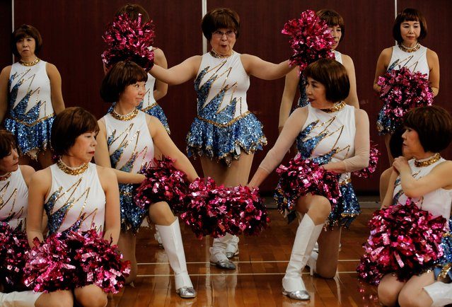 """Fumie Takino, 89, founder of a senior cheer squad called Japan Pom Pom, and other members pose for commemorative photos before filming a dance routine for an online performance in Tokyo, Japan, April 12, 2021. """"It's dancing; moving your body is nice"""", Takino said. """"And the costumes are unbelievably showy. Some people join just so they can wear them"""". (Photo by Kim Kyung-Hoon/Reuters)"""