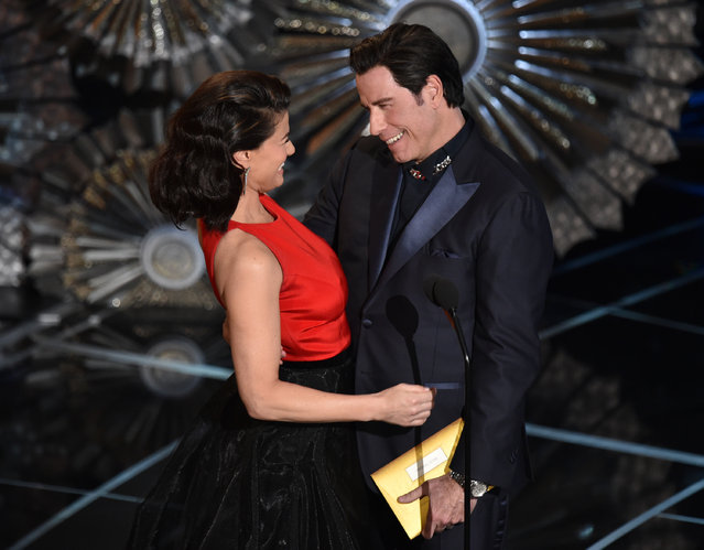 Idina Menzel, left and John Travolta present the award for best original song at the Oscars on Sunday, February 22, 2015, at the Dolby Theatre in Los Angeles. (Photo by John Shearer/Invision/AP Photo)