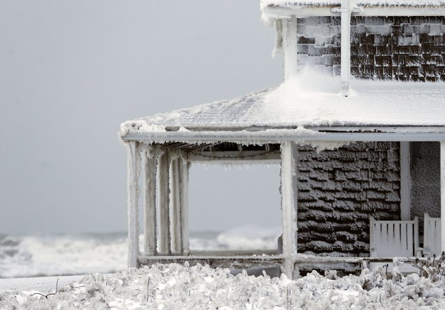 Frozen sea spray coats a house the day after a winter storm in Scituate, Mass., Wednesday, January 28, 2015. (Photo by Michael Dwyer/AP Photo)