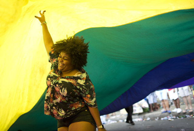 """A woman dances under a giant rainbow flag during the annual Gay Pride Parade along Copacabana beach in Rio de Janeiro, Brazil, Sunday, September 30, 2018. One week before Brazil's presidential elections, organizers coined the theme of the parade """"Vote for ideas and not for people"""", aiming to encourage people to vote for candidates who support gay and human rights. (Photo by Silvia Izquierdo/AP Photo)"""