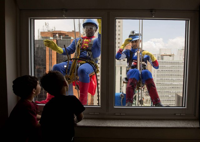 Young patients watch high rise window washers wearing Superman and Captain America costumes clean the windows of the Sabara Children's Hospital in Sao Paulo, Brazil, on Oktober 11, 2013. The hospital had their regular window washers dress up in super hero costumes to commemorate Children's Day. (Photo by Andre Penner/Associated Press)