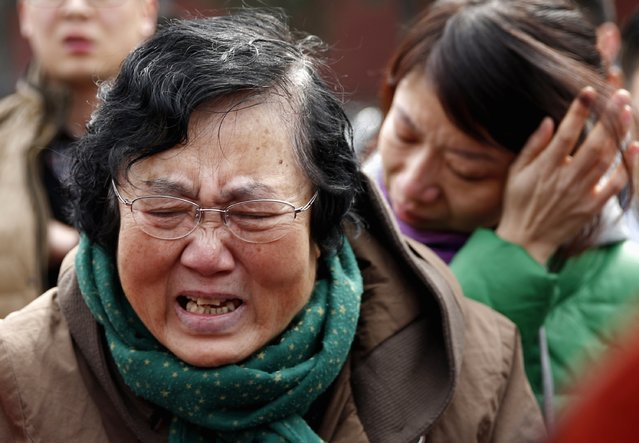Wang Guohui (L), mother of Li Zhi, a passenger of the missing Malaysia Airlines flight MH370, cries with daughter-in-law Catherine Gang during a gathering of family members of the missing passengers at Yonghegong Lama Temple in Beijing March 8, 2015. Malaysian and Chinese officials say they are committed to the search for MH370 and in assisting families who are still waiting for concrete information on what happened to their loved ones a year ago.    
