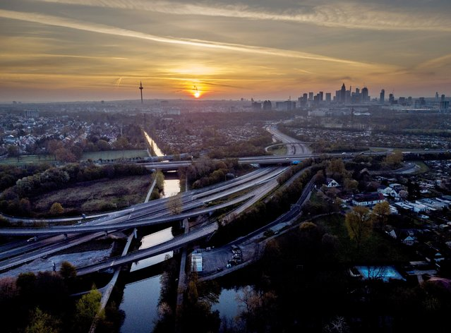 Almost empty highways lead to Frankfurt, Germany, as the sun rises on Saturday, April 24, 2021. From the weekend on a curfew becomes effective to avoid the outspread of the coronavirus. (Photo by Michael Probst/AP Photo)