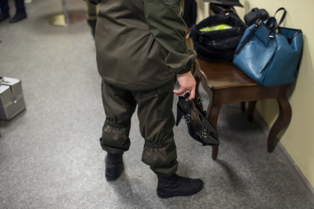 A female soldier of the self-proclaimed Donetsk People's Republic holds her high heels backstage during a beauty pageant to mark International Women's Day in Donetsk, March 7, 2015. (Photo by Marko Djurica/Reuters)